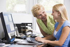 Woman and girl in home office with computer Royalty Free Stock Images