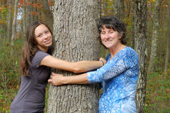 Woman and Girl Hugging Tree. Two generations of women express love of nature by hugging a tree Stock Photo