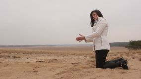 Woman girl kneels and throws sand autumn cold stock footage