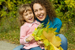 Woman and girl laugh with leaves in garden. Young woman and little girl laugh with leaves in hands in garden autumn Royalty Free Stock Photos