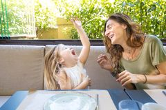 Woman and girl laughing out loud in restaurant. Happy family in restaurant: women mother and her daughter four years old blonde girl laughing out loud with funny Royalty Free Stock Photos