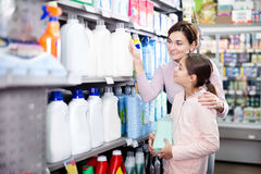 Woman with girl looking for cleaners in supermarket. Young women customer with girl looking for cleaners for home in the supermarket. Focus on woman Stock Image