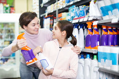 Woman with girl looking for cleaners in supermarket. Young women customer with girl looking for cleaners for a home in supermarket. Focus on both persons Stock Image