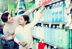 Woman with girl looking for cleaners in supermarket. Young women customer with girl looking for a cleaners for home in supermarket. Focus on child Royalty Free Stock Image
