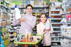 Woman with girl looking for cleaners in supermarket. Young women customer with girl looking for a cleaners for home in the supermarket. Focus on child Royalty Free Stock Photo
