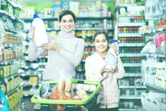 Woman with girl looking for cleaners in supermarket. Young women customer with girl looking for a cleaners for home in the supermarket. Focus on child Stock Images