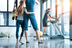 Woman with girl looking at handsome man workout on treadmill Royalty Free Stock Images