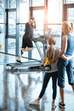 Woman with girl looking at handsome man workout on treadmill Royalty Free Stock Image