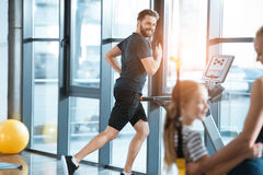 Woman with girl looking at handsome man workout on treadmill Stock Photos