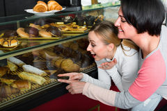 Woman and girl looking into the pastry shop window Stock Photography