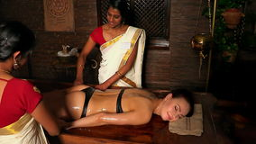 Woman girl lying on her stomach and having spa treatment. Two real Indian masseuses massage hands. stock footage