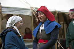 Woman and a girl in medieval costume talking. Royalty Free Stock Images