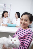 Woman and girl with pet dog in veterinarian's office Stock Photo