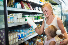 Woman and girl picking fresh dairy products in refrigerated sect. Happy positive women and  smiling girl picking fresh dairy products in refrigerated section in Royalty Free Stock Image