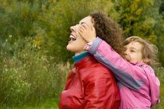 Woman and girl playing in garden, girl closes eyes Stock Photos
