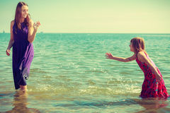 Woman and girl playing in water Royalty Free Stock Photography