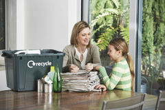 Woman And Girl Preparing Waste Paper For Recycling. At home Royalty Free Stock Photos