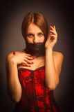 Woman girl in red corset, her mouth covered Royalty Free Stock Photography