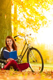 Woman girl relaxing in autumnal park reading book Royalty Free Stock Photography