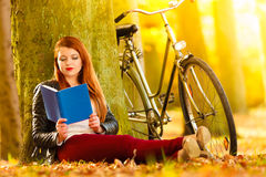 Woman girl relaxing in autumnal park reading book Royalty Free Stock Images