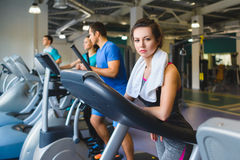 Woman girl resting at the gym on a cross trainer Royalty Free Stock Photos