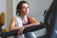 Woman girl resting at the gym on a cross trainer Stock Image