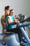 Woman girl resting at the gym on a cross trainer Stock Photos