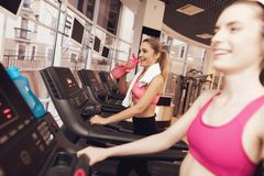 Woman and girl running on treadmill at the gym. They look happy, fashionable and fit. Woman and girl in sportswear running on treadmill at the gym. They look Royalty Free Stock Image
