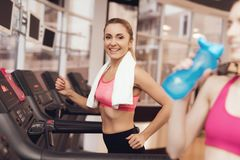 Woman and girl running on treadmill at the gym. They look happy, fashionable and fit. Woman and girl in sportswear running on treadmill at the gym. They look Royalty Free Stock Photography