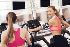 Woman and girl running on treadmill at the gym. They look happy, fashionable and fit. Woman and girl in sportswear running on treadmill at the gym. They look Royalty Free Stock Photos