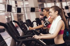 Woman and girl running on treadmill at the gym. They look happy, fashionable and fit. Woman and girl in sportswear running on treadmill at the gym. They look Royalty Free Stock Images