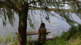 Woman girl sit bench willow tree move wind lake recreation relax. Woman girl sit on wood bench under willow tree branch move in wind near lake. recreational stock footage