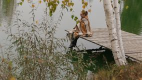 Woman girl sit on wooden bench under willow tree branch move in wind near lake stock footage