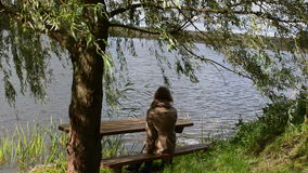 Woman girl sit wooden bench willow tree move wind lake relax. Woman girl sit on wooden bench under willow tree branch move in wind near lake. recreational recess stock footage