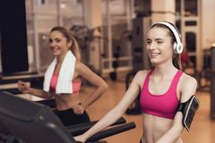 Woman and girl running on treadmill at the gym. They look happy, fashionable and fit. Woman and girl in sportswear running on treadmill at the gym. They look Stock Photo