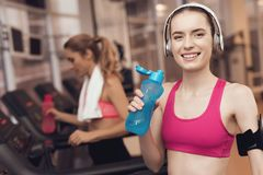 Woman and girl running on treadmill at the gym. They look happy, fashionable and fit. stock image