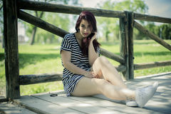 Woman,  girl with straw hat sitting on a wooden bridge in a park Royalty Free Stock Photos