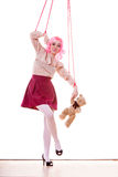 Woman girl stylized like marionette puppet on string. Mental disorder concept. Young woman girl stylized like marionette puppet on string with teddy bear toy Royalty Free Stock Photo
