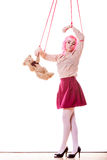 Woman girl stylized like marionette puppet on string. Mental disorder concept. Young woman girl stylized like marionette puppet on string with teddy bear toy Stock Image