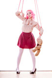 Woman girl stylized like marionette puppet on string. Mental disorder concept. Young woman girl stylized like marionette puppet on string with teddy bear toy Royalty Free Stock Images