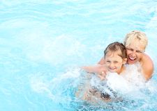 Woman and  girl swimming in the pool. Middle-aged women and a little girl swimming in the pool with hydro-massage Stock Photo