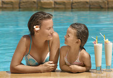 Woman and girl in the swimming pool. With cocktail Stock Image
