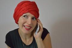 Beautiful Gypsy - Eastern woman in red turban, gir. The woman - girl talking on the phone Stock Image