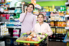 Woman with girl telephoning to consult about shopping. Young women customer with girl telephoning to consult about shopping in supermarket. Focus on the girl Royalty Free Stock Photography