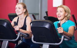 Woman and girl training on exercise bikes Stock Photo