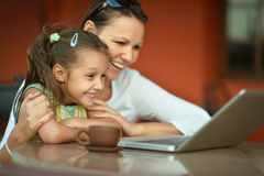 Woman with girl using laptop Stock Photo