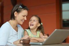 Woman with girl using laptop Stock Photos