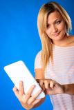Woman girl using tablet touchpad reading e-book e-reader on blue. Modern young woman using tablet touchpad. Blond girl reading e-book e-reader on blue Royalty Free Stock Photography