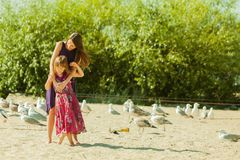 Mother and daughter on beach near boat Stock Photography