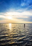 Woman girl walking in the sea at sunset, dawn Royalty Free Stock Photo